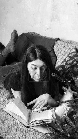 Photo pour Étudiant lisant un livre dans une chambre confortable. Une fille tenant un livre. Concept : lire un livre - image libre de droit