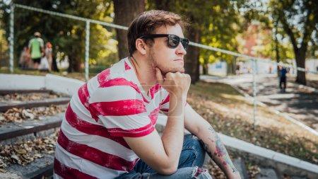 Photo pour Un jeune homme en tenue décontractée est assis sur les marches du parc et regarde autour de lui. - image libre de droit
