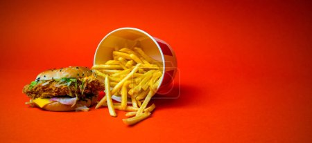 Photo for Greasy burger and french fries from a fast food restaurant isolated on a orange background, copy space - Royalty Free Image
