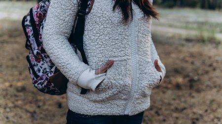 Photo pour La femme a mis ses mains dans ses poches pour se tenir au chaud par une froide journée d'automne.. - image libre de droit