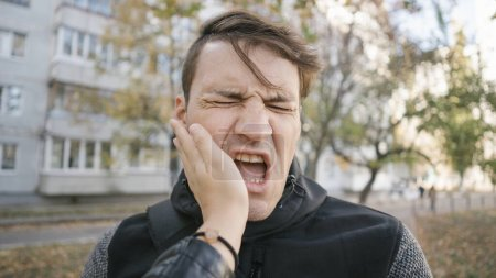 Photo for Unhappy scared man getting slapped standing into the park - Royalty Free Image