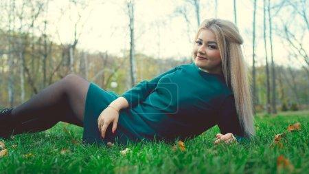 Photo pour Portrait d'une belle fille allongée sur l'herbe. Une charmante femme s'allonge sur l'herbe verte avec des feuilles jaunes - image libre de droit