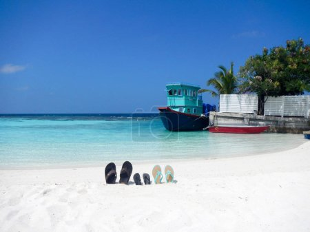 Three pairs of flip flops sandals on a Maldive beach propped up in the sand with an old fishing boat at a quay behind and palm trees in a concept of an idyllic family summer vacation