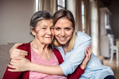Photo for Portrait of an elderly grandmother with an adult granddaughter sitting on the sofa at home, hugging. - Royalty Free Image