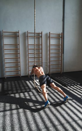 Photo for Young fit man in gym working out with climbing rope. Rear view. - Royalty Free Image