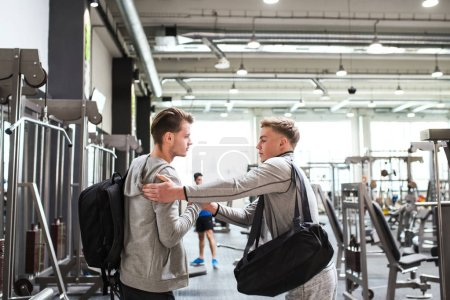 Photo for Young male friends with bags in modern crossfit gym, greeting each other. - Royalty Free Image