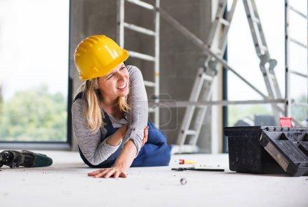 Foto de Accidente de una trabajadora en la obra. Una mujer lesionada en el piso. - Imagen libre de derechos