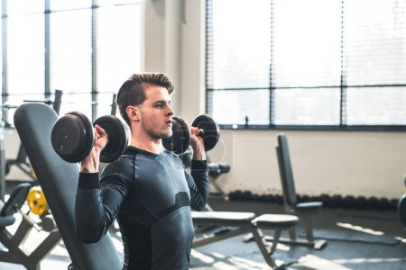 Photo for Young fit men doing strength training, exercising with dumbbells in modern gym. Copy space. - Royalty Free Image