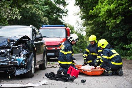 Photo pour Pompiers aidant une jeune femme après un accident de voiture. Une conductrice dans un brancard en plastique sur la route de campagne. - image libre de droit