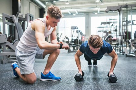 Photo for Young fit men friends in gym doing push ups on dumbbells, measuring time on smartwatch. - Royalty Free Image