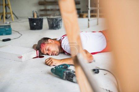 Foto de Un trabajador hombre inconsciente tirado en el suelo después de un accidente en la obra, sangre en la cabeza. Trabajar sin un concepto de lesión en la cabeza y casco. - Imagen libre de derechos