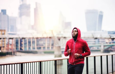 Photo for Young sporty black man runner with smartwatch and earphones running on the bridge outside in a city. - Royalty Free Image