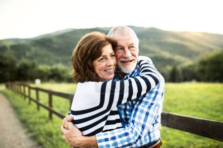 Photo for A close-up of a joyful senior couple hugging outside in nature. - Royalty Free Image
