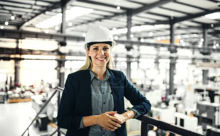 Photo for A portrait of a young industrial woman engineer standing in a factory. - Royalty Free Image