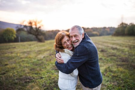 Photo for Senior couple in love on a walk in an autumn nature. Senior man and a woman hugging at sunset. Copy space. - Royalty Free Image