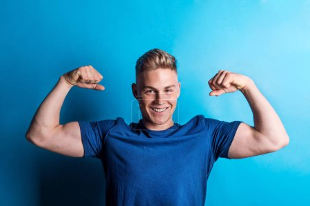 Photo for Portrait of a young cheerful man in a studio standing on a blue background, flexing muscles. - Royalty Free Image