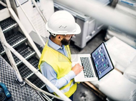 Photo pour Portrait d'un ingénieur industriel mature avec ordinateur portable dans une usine, travaillant. Vue grand angle . - image libre de droit