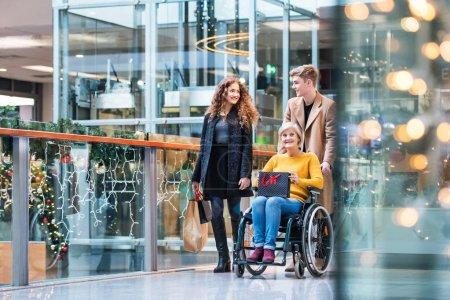 Photo pour Une grand-mère senior en chaise roulante et petits-enfants adolescents avec des sacs de papier marche dans le centre commercial au moment de Noël. - image libre de droit