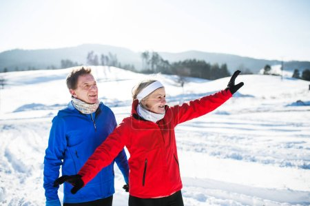 Photo for Senior couple runners standing outside in winter nature, resting. - Royalty Free Image