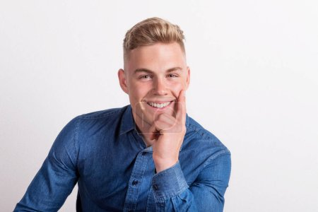 Photo for Portrait of a happy young man in a studio, wearing blue denim shirt. - Royalty Free Image