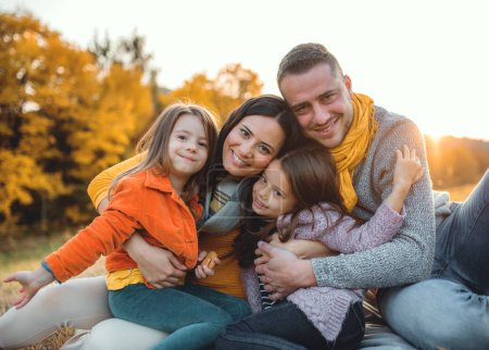 Photo for A portrait of happy young family with two small children sitting on a ground in autumn nature at sunset. - Royalty Free Image