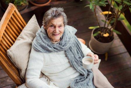 Photo pour Une vue de dessus d'une femme âgée avec une tasse de thé ou de café assis à l'extérieur sur une terrasse par une journée ensoleillée en automne . - image libre de droit