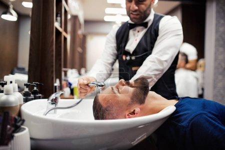 Photo pour Beau hipster homme client visitant coiffeur et coiffeur dans le salon de coiffure . - image libre de droit