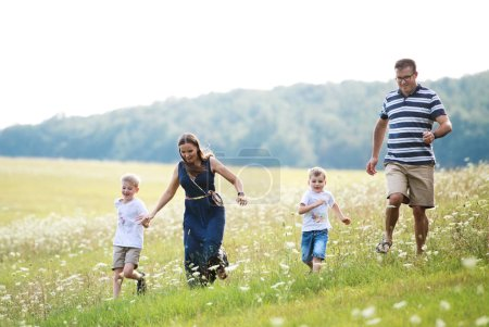 Photo for A young family with two small cheerful sons walking in nature on a summer day. - Royalty Free Image