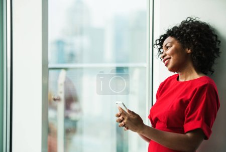 Photo for A portrait of happy woman standing by the window, holding smartphone. Copy space. - Royalty Free Image