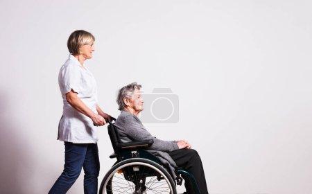 Photo pour Portrait en studio d'une heureuse aînée en fauteuil roulant et d'une infirmière. Espace de copie . - image libre de droit