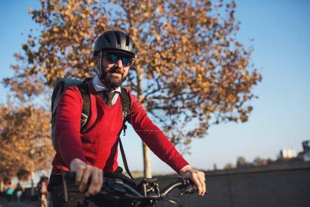 Hipster-Geschäftsmann pendelt mit dem Fahrrad zur Arbeit in die Stadt.