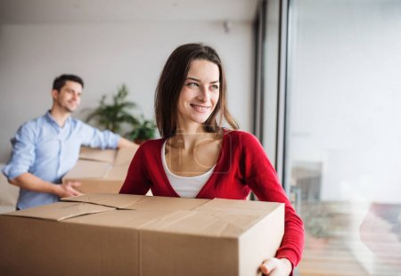 Photo for Young happy couple with cardboard boxes moving in a new home. - Royalty Free Image