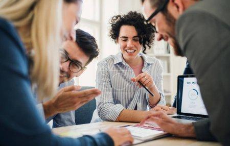 Foto de Grupo de jóvenes empresarios concentrados hombres y mujeres con portátil trabajando juntos en una oficina moderna . - Imagen libre de derechos