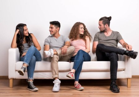 Photo for Portrait of young group of cheerful friends sitting on a sofa in a studio, talking. - Royalty Free Image