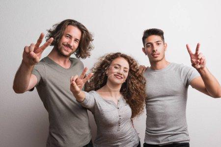 Photo pour Portrait de jeune fille joyeuse avec deux copains debout dans un studio, doigts formant V pour la victoire . - image libre de droit