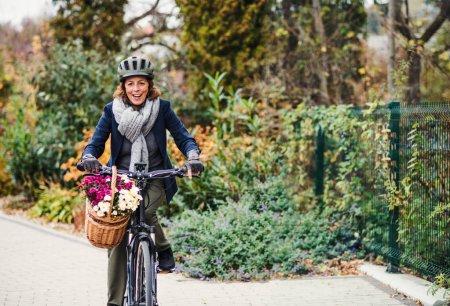 Photo pour Une femme senior active avec casque et electrobike vélo à l'extérieur de la ville. Espace copie. - image libre de droit