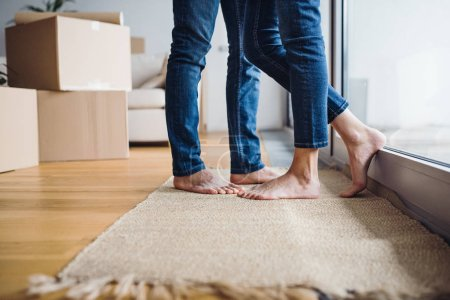 Photo for A midsection of legs and feet of young couple moving in a new home, standing by a window. - Royalty Free Image