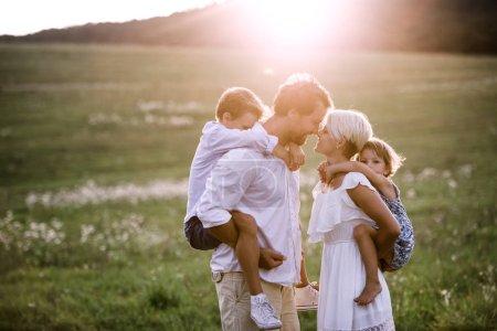 Młode rodziny z małymi dziećmi w lato natura o zachodzie słońca.