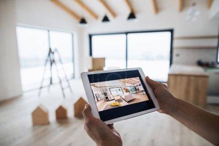 Photo pour Une section médiane de l'homme avec tablette, en regardant des croquis de design d'intérieur. Un nouveau concept de maison . - image libre de droit