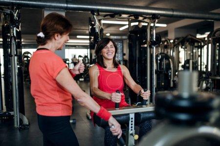 Photo pour Deux amis joyeux femmes âgées dans la salle de gym faire des exercices d'entraînement force. - image libre de droit