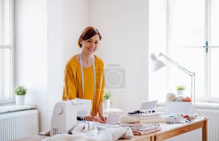 Photo for Young creative woman working in a studio, startup of small tailoring business. - Royalty Free Image
