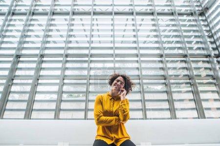 Photo pour Portrait d'une jeune étudiante ou d'une jeune femme d'affaires assise sur un bureau dans une bibliothèque ou un bureau, à l'aide d'un téléphone intelligent . - image libre de droit