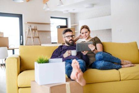 Photo pour Un jeune couple avec tablette et tasse de café assis sur le canapé, emménageant dans une nouvelle maison . - image libre de droit