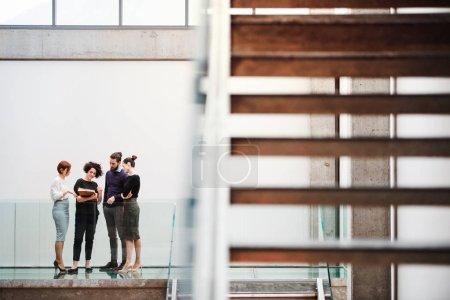 Photo pour Un groupe de jeunes hommes d'affaires restant près de l'escalier, parlant. - image libre de droit