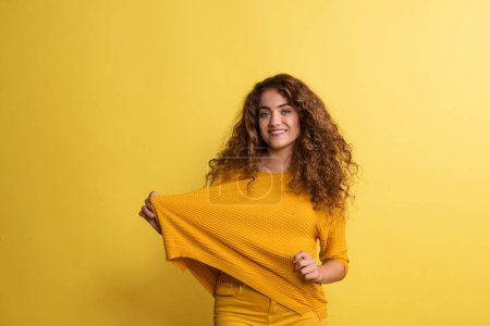 Photo pour Portrait d'une jeune femme dans un studio sur fond jaune, s'amusant . - image libre de droit