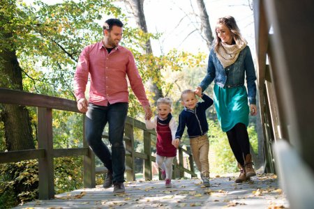 Photo for A beautiful young family with small twins on a walk in autumn forest, holding hands. - Royalty Free Image
