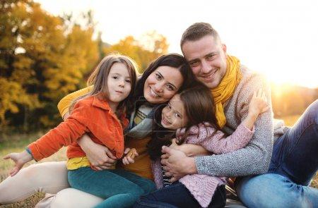 Photo pour Portrait d'une jeune famille heureuse avec deux jeunes enfants assis sur un sol en automne nature au coucher du soleil . - image libre de droit
