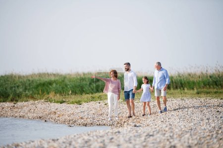 Photo for A multigeneration family on a holiday walking by the lake, holding hands. - Royalty Free Image