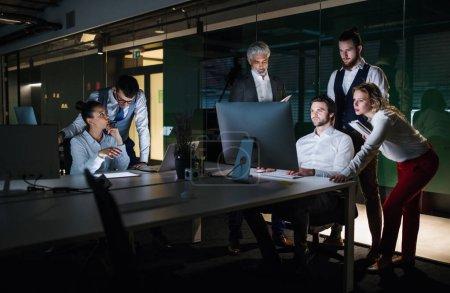 Photo pour Un groupe de gens d'affaires dans un bureau le soir ou la nuit, en utilisant un ordinateur . - image libre de droit