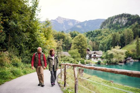 Photo for An active senior pensioner couple hiking in nature, holding hands. - Royalty Free Image